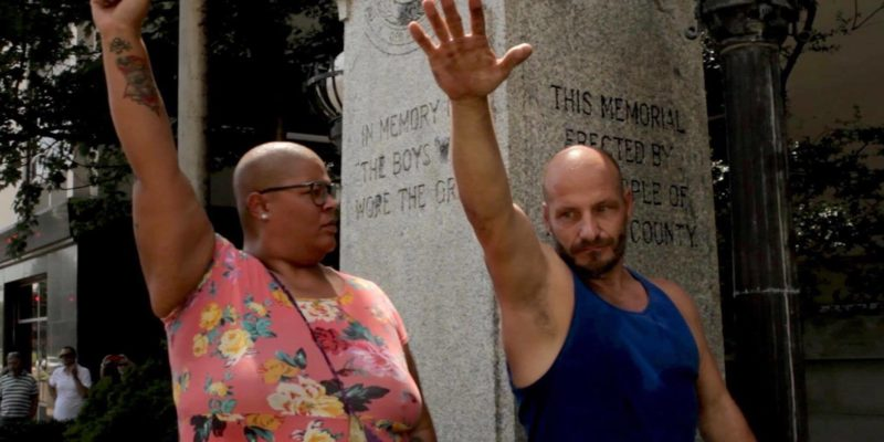 An African American woman with her fist in the air looks a white man giving a Nazi salute