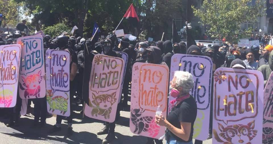 """Black clad demonstrators with """"NO HATE"""" signs"""