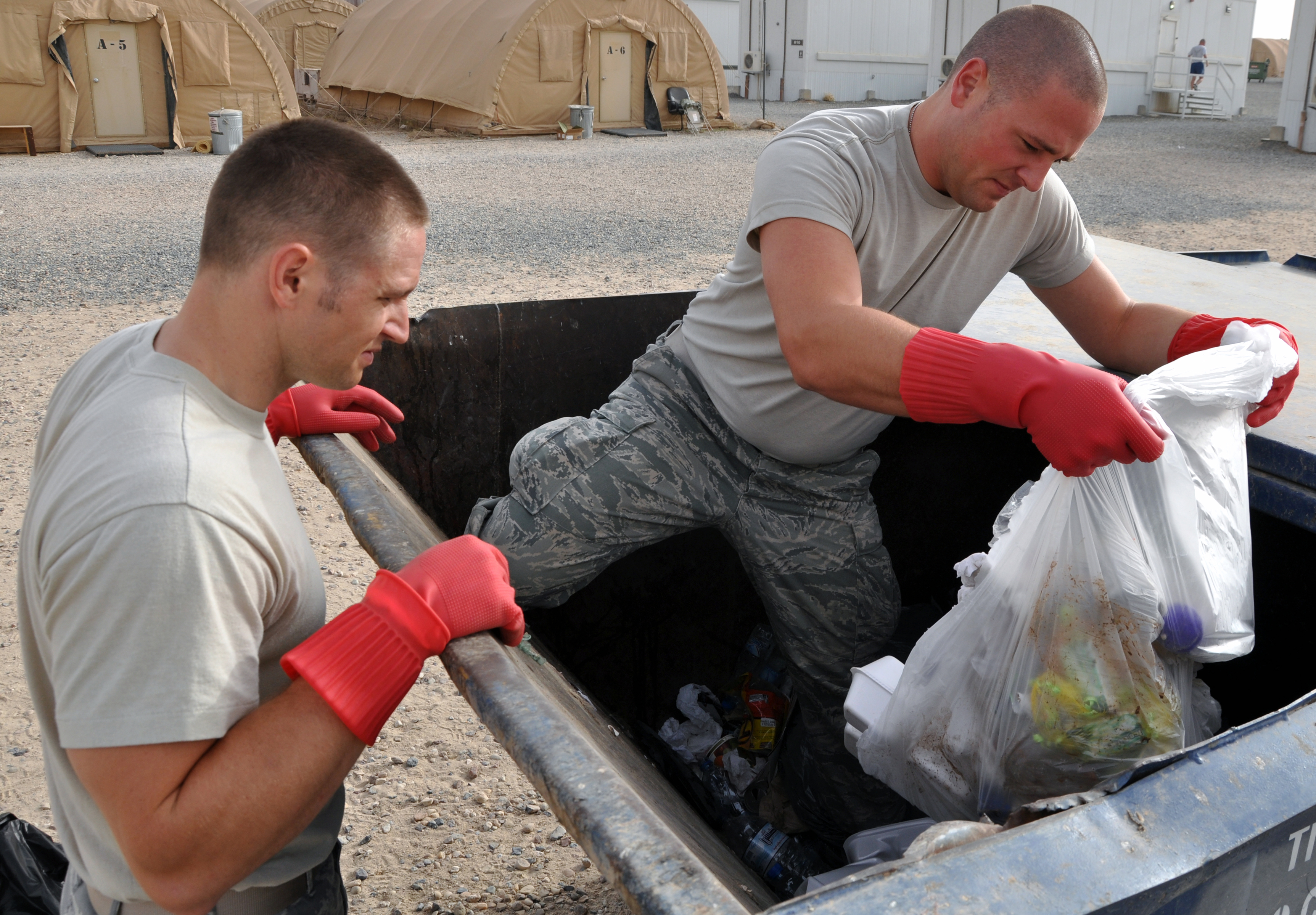Two men in fatigues, one standing in the garbage bin