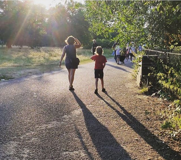Mother and son walking away from the camera in a park, with long shadows behind them