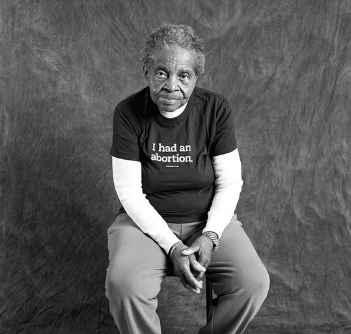 "A Black woman in her 80s wearing a t-shirt that says ""I had an abortion."""