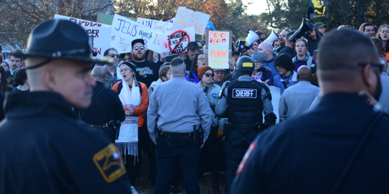 Crowd of protesters facing sheriffs deputies and riot police