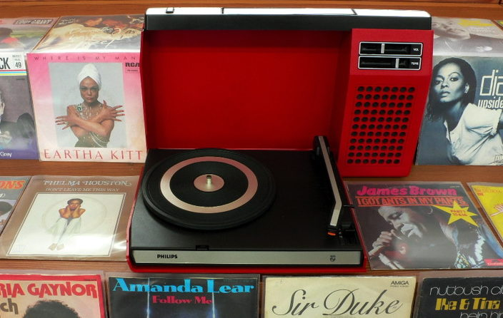 plastic record player surrounded by albums